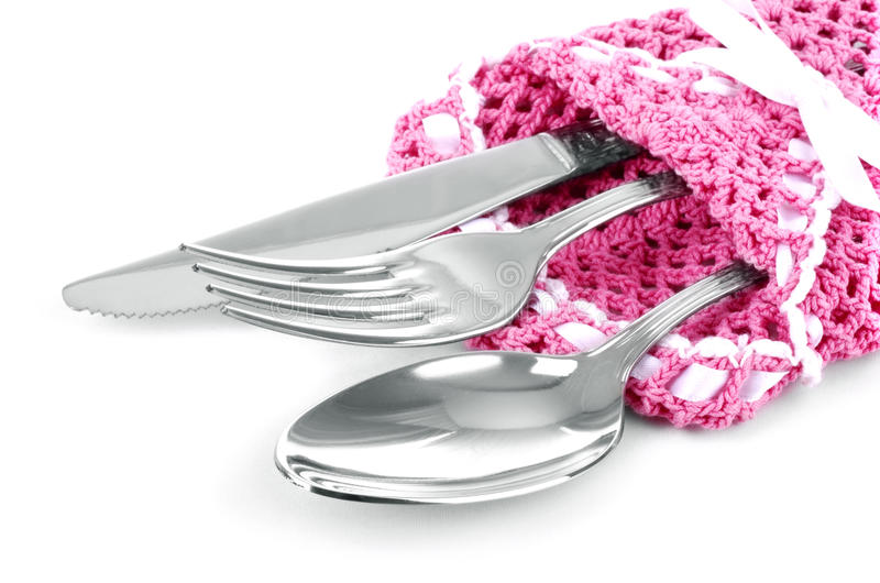 刀子、叉子和匙子在桃红色编织了被隔绝的餐巾 免版税库存图片