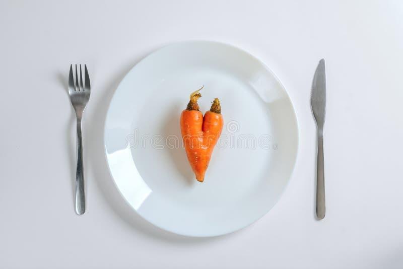 刀子、叉子和红萝卜在心脏在一块白色板材塑造在白色背景,顶视图 免版税图库摄影