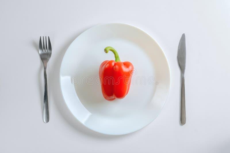 刀子、叉子和红辣椒,在一块白色板材的paprica在白色背景,顶视图 图库摄影