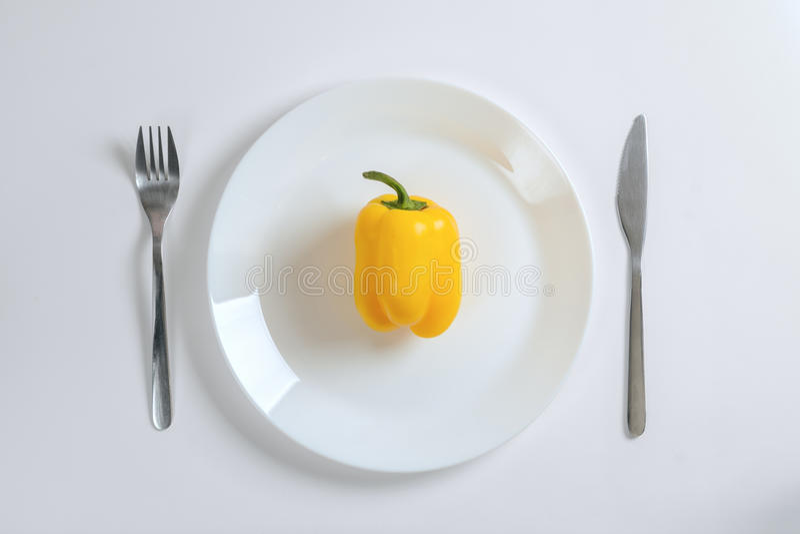刀子、叉子和黄色胡椒,在一块白色板材的paprica在白色背景,顶视图 图库摄影