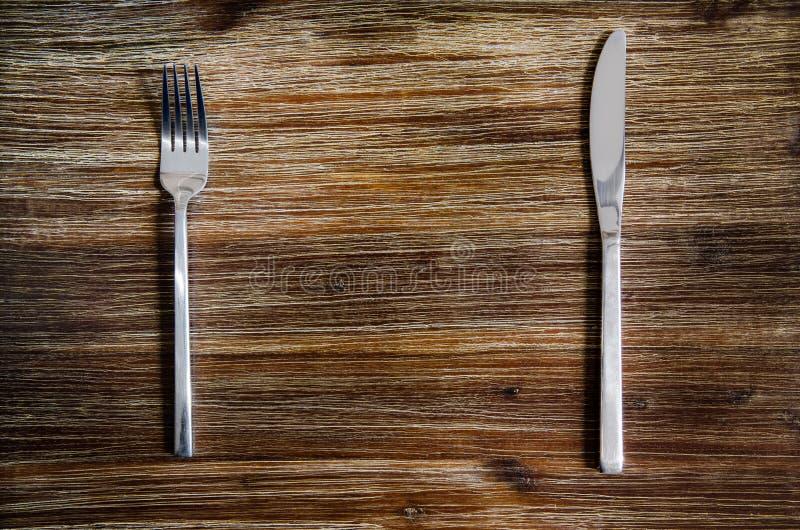 刀子和叉子在一张木桌上设置了 免版税库存图片