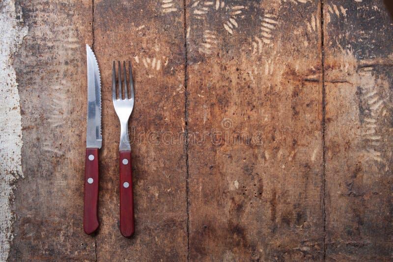 刀子和叉子在木背景 在木的利器 库存照片