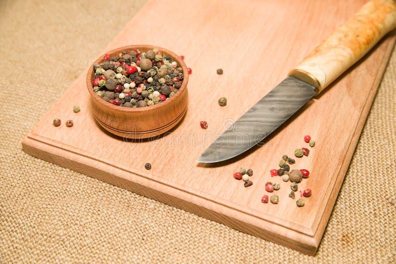 刀子,胡椒五谷混合物木表面上的 免版税库存照片