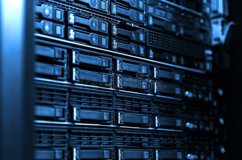 刀片服务器设备机架的关闭在与被弄脏的侧壁冷的蓝色口气的大数据中心 免版税库存照片