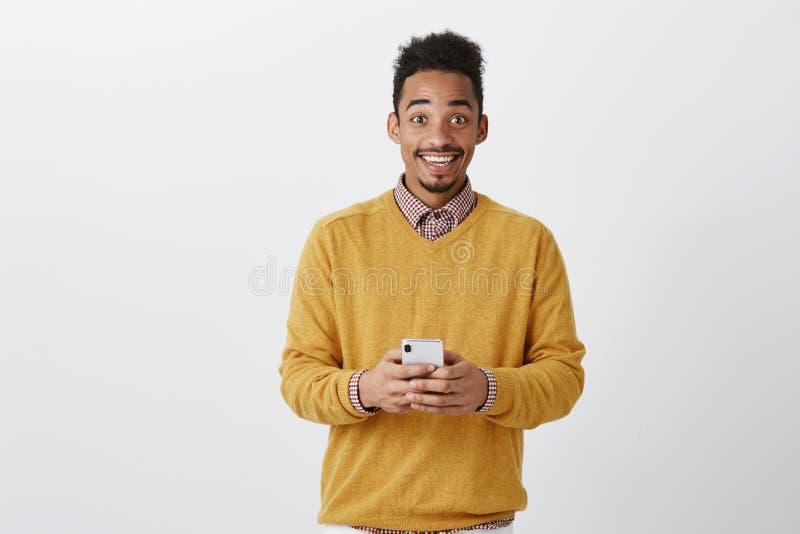 分享了不起的新闻与朋友 愉快的兴奋的深色皮肤的人画象时髦成套装备的,拿着智能手机,注视 免版税库存图片