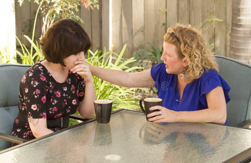分享和聊天在咖啡的两名妇女 免版税库存图片