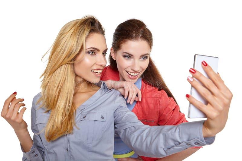 分享在一个巧妙的电话的两名妇女社会媒介 免版税库存照片
