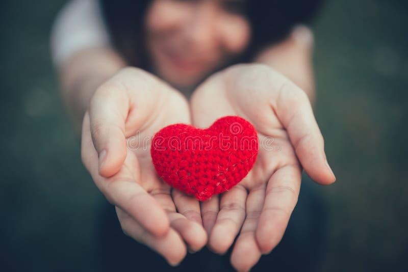 分享在妇女手上的爱和心脏红颜色在华伦泰` s天 免版税库存图片