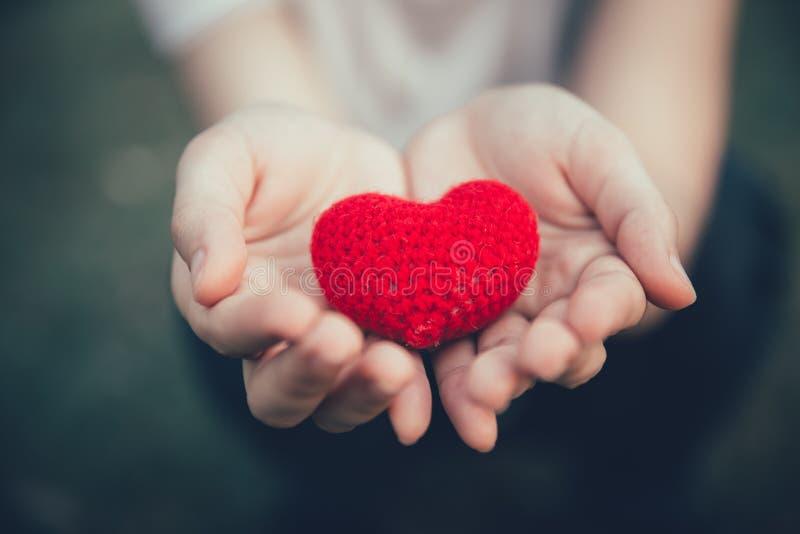 分享在妇女手上的爱和心脏红颜色 免版税库存图片