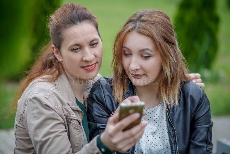 分享在巧妙的电话的两个妇女朋友社会媒介户外 库存照片