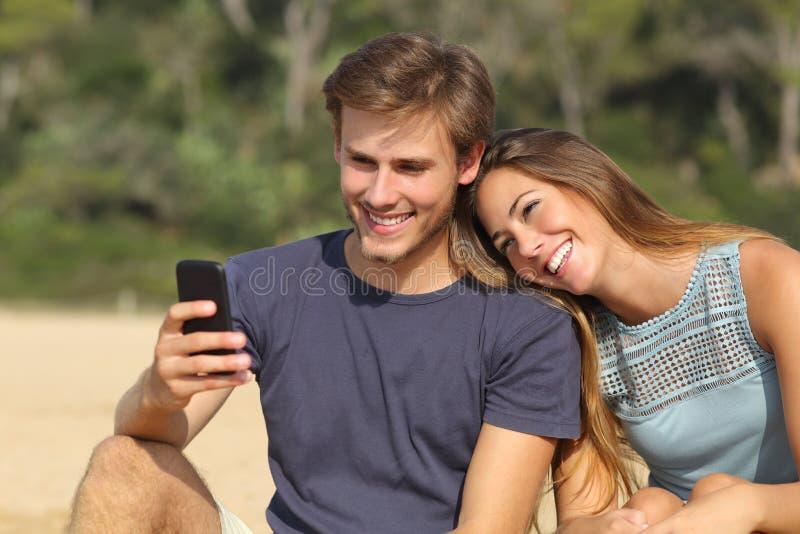 分享在巧妙的电话的少年夫妇社会媒介 免版税图库摄影