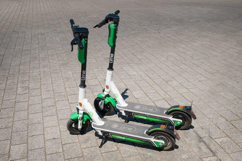 分享在边路的乘驾的电滑行车、escooter或者e滑行车公司石灰 免版税库存图片