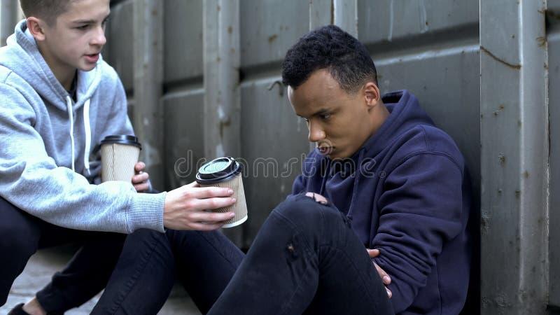 分享温暖的咖啡的男孩与冻无家可归的少年,慈善志愿者 免版税库存照片