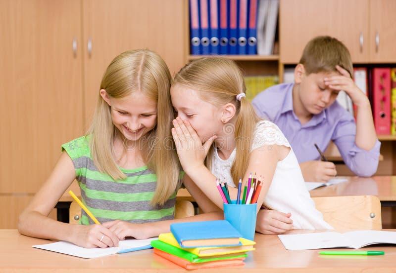 分享秘密的女孩在教室 免版税库存图片