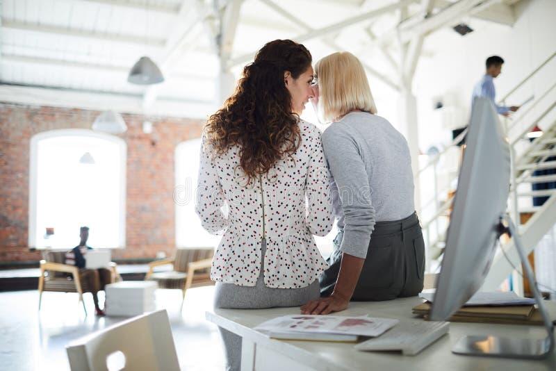 分享秘密的妇女在办公室 免版税库存照片