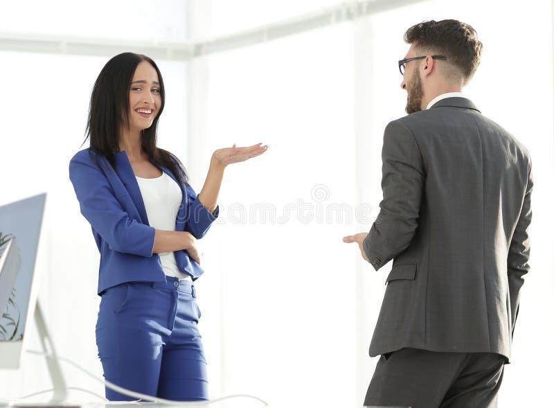 分享笑话的愉快的笑的年轻女实业家与男性co 免版税库存照片