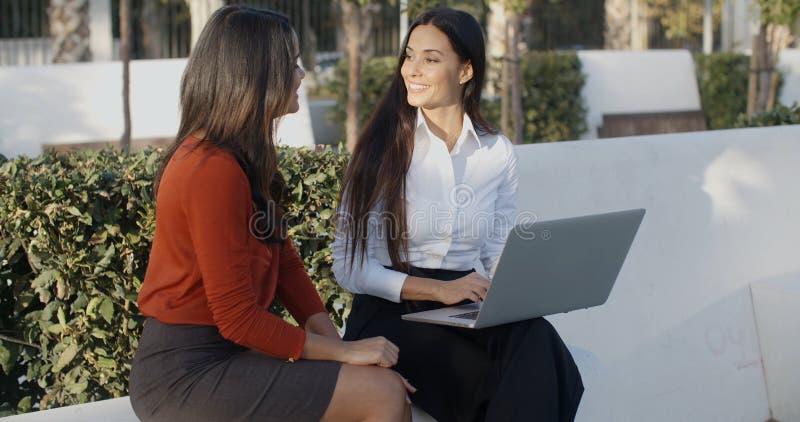 分享膝上型计算机的两名俏丽的妇女户外 库存图片