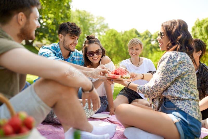 分享西瓜的愉快的朋友在夏天野餐 库存图片