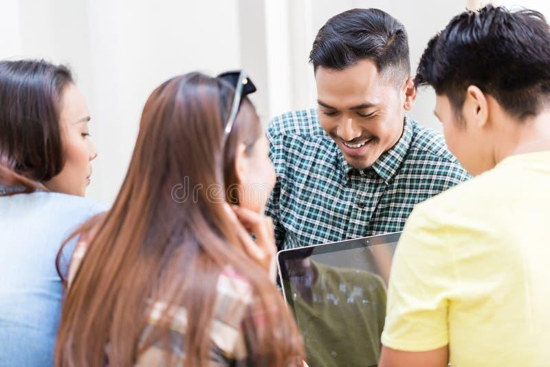 分享观点和信息的四名年轻雇员在办公室 免版税库存照片