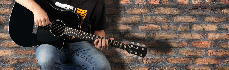 分割人弹在老砖墙背景的一把黑声学吉他 库存图片