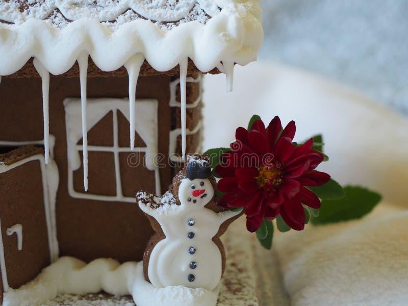 分割房子,与红色花的姜饼雪人在华而不实的屋前面 免版税库存图片