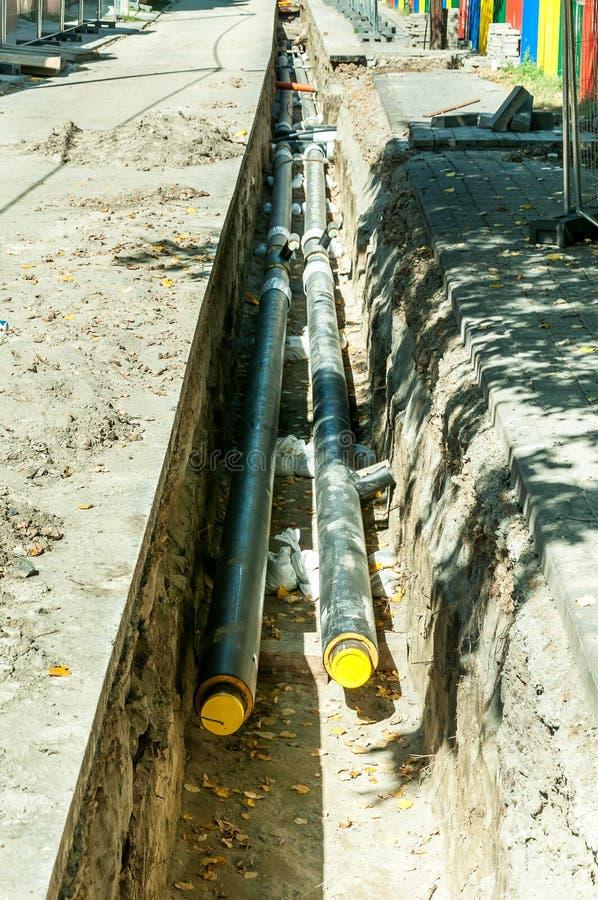 分区供暖管道赔偿和重建与有建造场所安全网篱芭的街道平行 库存图片