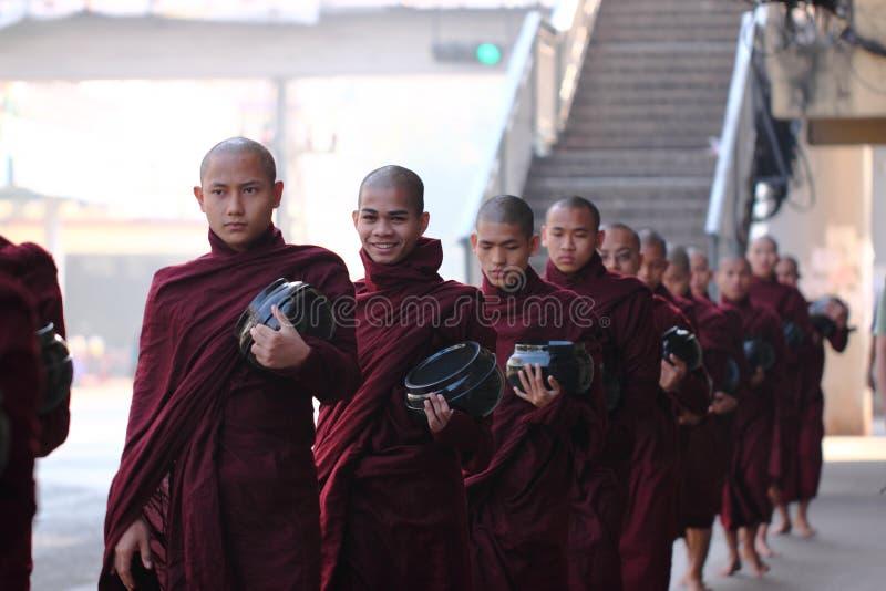 分布的食物传统救济仪式对和尚的在仰光,缅甸街道上  免版税库存图片