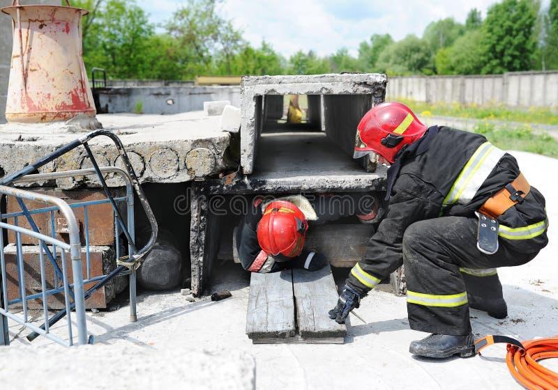 分开救助者和志愿者和军事寻找生活的瓦砾 示范性的锻炼 库存图片
