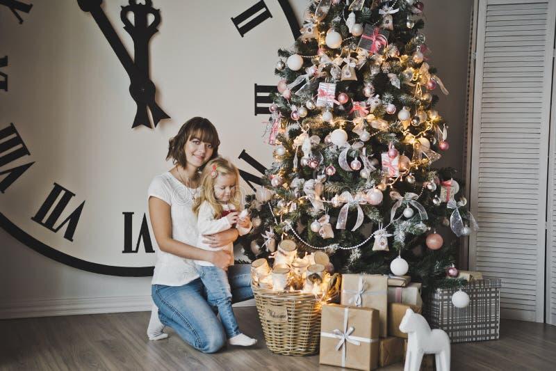 分开母亲和女儿礼物在圣诞树732下 库存照片