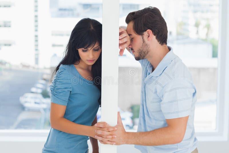 分开的夫妇由白色墙壁分离 免版税图库摄影