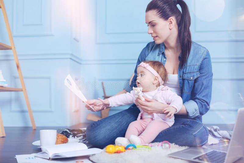 分散她的母亲的好逗人喜爱的女孩与工作 免版税库存照片