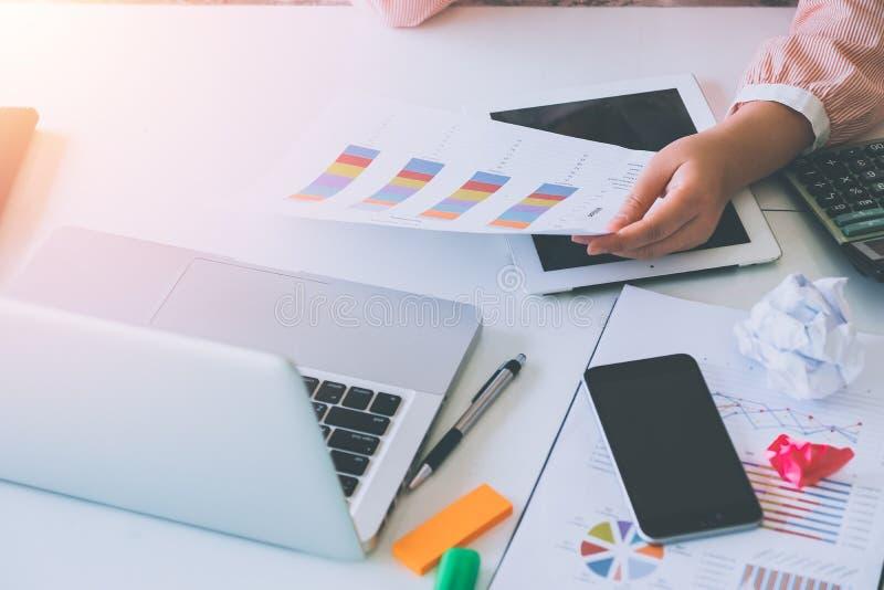 分析与便携式计算机的女商人投资图 免版税库存图片