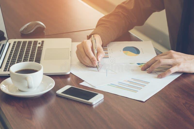 分析与膝上型计算机和咖啡的商人图表文件在办公室葡萄酒口气 库存照片
