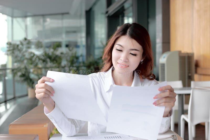 分析图或文书工作在她的手上的确信的年轻亚裔女商人画象在办公室 免版税图库摄影