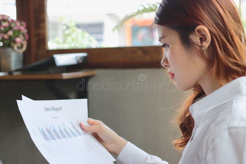 分析图或文书工作的专业年轻亚裔女商人在办公室 免版税图库摄影