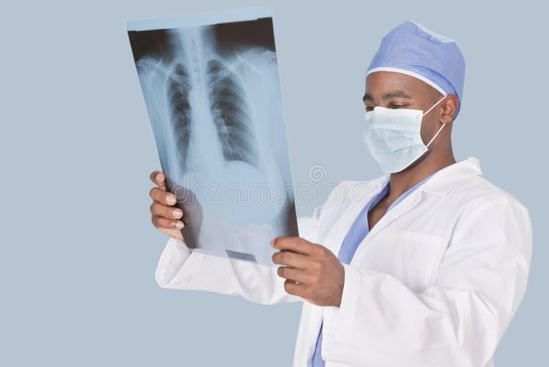 分析在浅兰的背景的男性外科医生X-射线报告 库存照片
