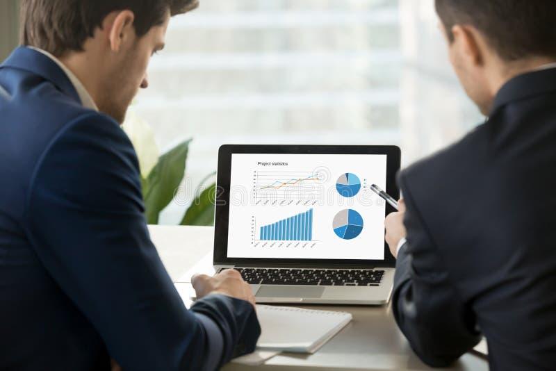分析在膝上型计算机屏幕上的两个商人项目统计 免版税图库摄影