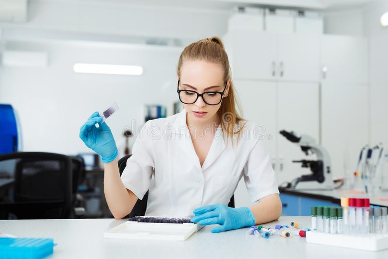 分析显微镜幻灯片的科学家在实验室 女性工作在有显微镜的实验室 研究员审查 库存照片