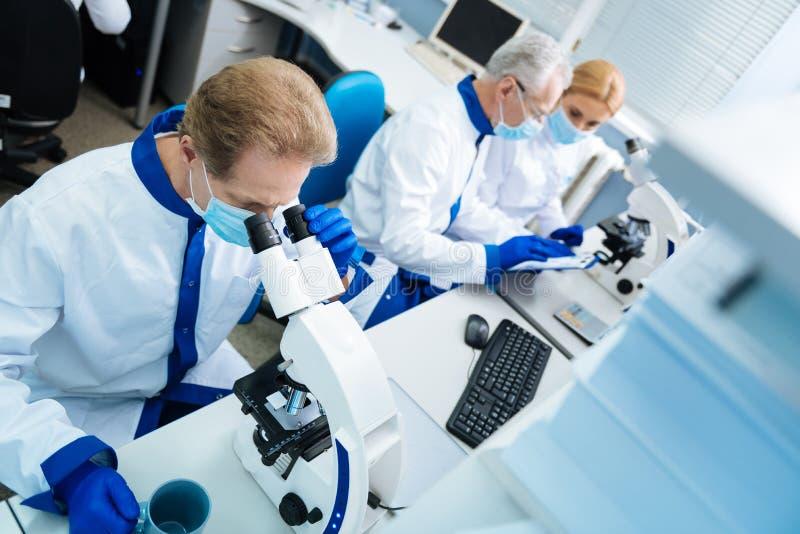 分析染色体的严肃的科学家在实验室里 库存照片