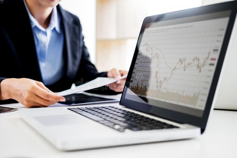 分析股票交易市场图表在计算机显示器屏幕上的投资图的财政报告投资者在办公室 免版税库存图片