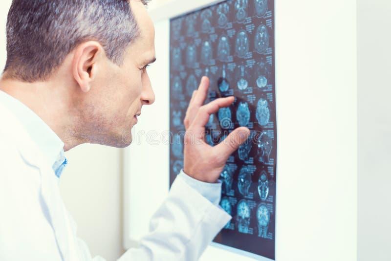 分析计算机控制X线断层扫描术扫描的被集中的医生 免版税库存图片