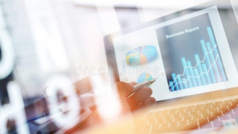 分析销售数据和指向企业图表图成长和进展的商人在膝上型计算机屏幕上 E 库存照片