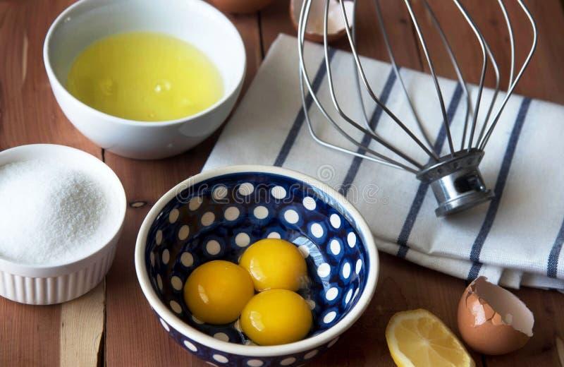 分离鸡蛋和和准备卵黄质在一点碗的扫的蛋白和卵黄质 库存照片