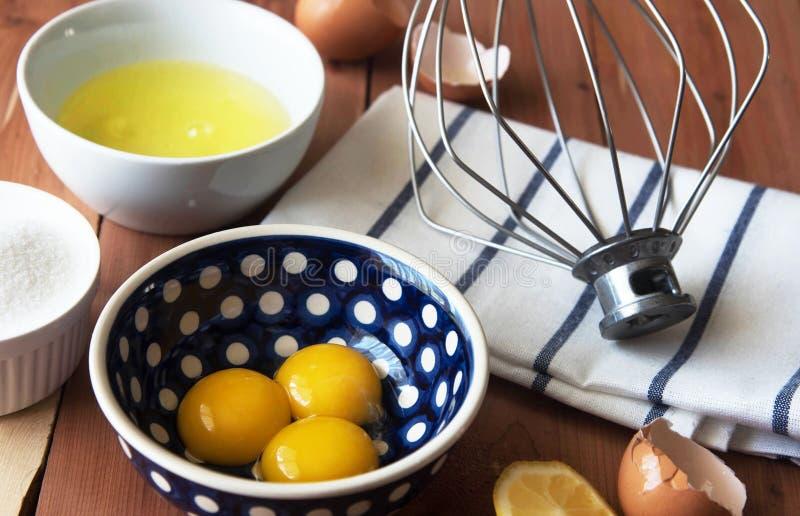 分离鸡蛋和和准备卵黄质在一点碗的扫的蛋白和卵黄质 免版税库存照片