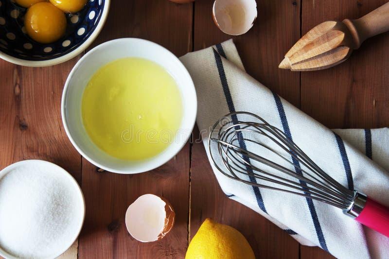 分离鸡蛋和和准备卵黄质在一点碗的扫的蛋白和卵黄质 免版税图库摄影