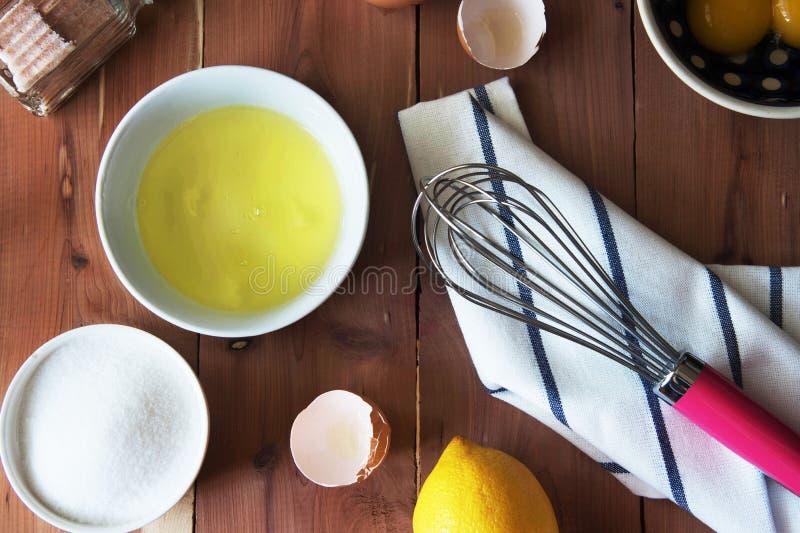 分离鸡蛋和和准备卵黄质在一点碗的扫的蛋白和卵黄质 库存图片
