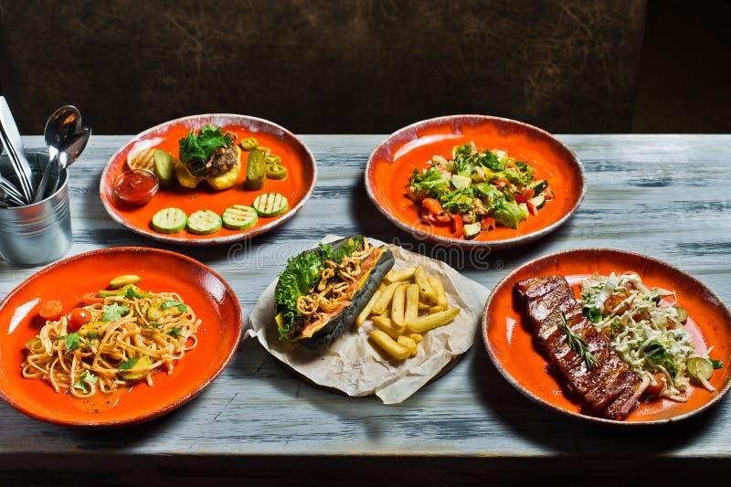 分类各种各样的食物格栅、肉、bbq党费斯特热狗、烤肉排骨、牛排、Carbonara浆糊和螃蟹沙拉 库存图片