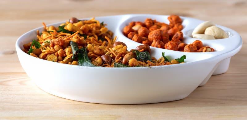 分类咸嘎吱咬嚼的印度混合Nimco或Namkeen和辣上漆的花生白色碗木背景 免版税图库摄影