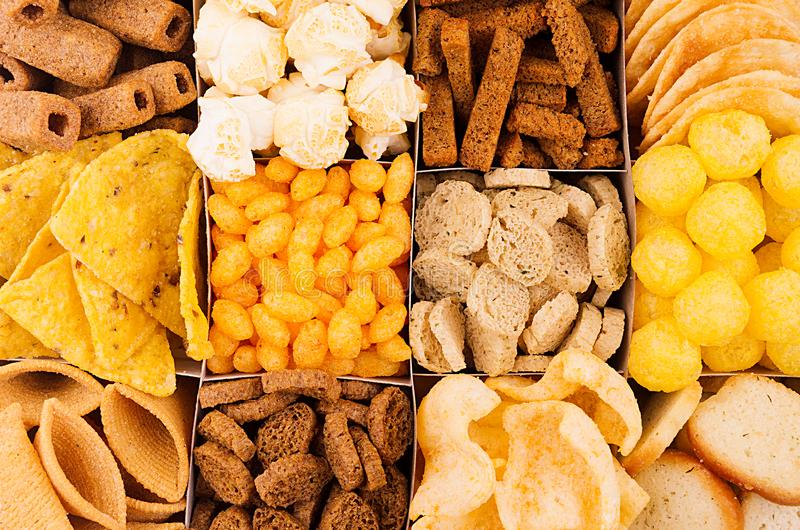 分类嘎吱咬嚼的快餐-玉米花,烤干酪辣味玉米片,油煎方型小面包片,玉米黏附,在细胞的土豆片作为装饰背景,顶视图, clos 库存图片