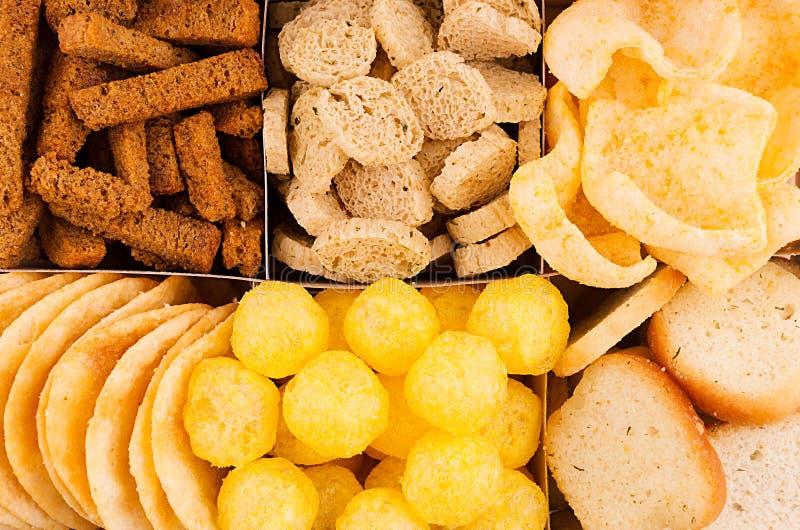 分类嘎吱咬嚼的快餐-玉米花,烤干酪辣味玉米片,油煎方型小面包片,玉米黏附,在细胞的土豆片作为装饰背景,顶视图 免版税库存照片